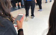 student walking in the hallway while texting